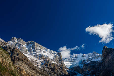 Snow-covered majestic mountain peaks with dark blue sky and flowing clouds in the background. Valley of the Ten Peaks, Moraine lake. Banff National Park, Canadian Rockies, Alberta, Canada.