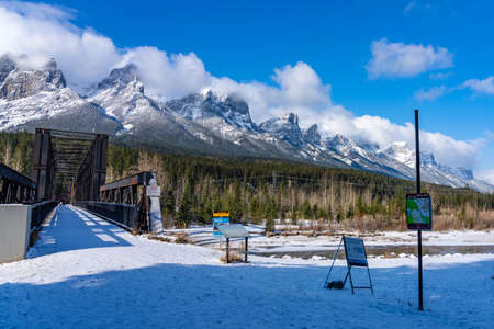 Canmore, AB, Canada-OCT 24 2020: Canmore Engine Bridge in early winter season sunny day morning. Clear blue sky, snow capped Mount Rundle mountain range in background. Sajtókép