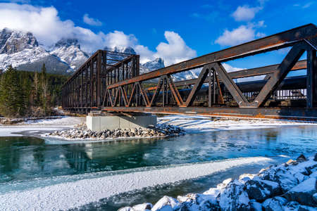 Drift ice floating on Bow River in early winter season sunny day morning. Clear blue sky, snow capped Mount Rundle mountain range in background. Landscape in Canmore Engine Bridge, Alberta, Canada.