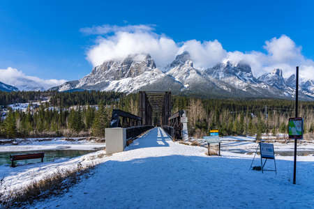 Canmore Engine Bridge in early winter season sunny day morning. Clear blue sky, snow capped Mount Rundle mountain range in background.