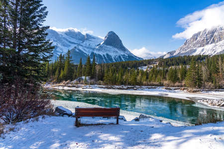 Natural scenery in early winter season sunny day morning. Drift ice floating on Bow River. Clear blue sky, snow capped Mount Lawrence Grassi in background. Landscape in Town Canmore, Alberta, Canada. Stock fotó