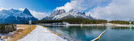 Canmore, AB, Canada-OCT 24 2020: Rundle Forebay Reservoir in winter sunny day morning. Clear blue sky, snow capped Mount Rundle and Mount Lawrence Grassi mountain range in background.