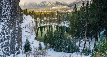 Upper and Lower Grassi Lakes in winter season, Town of Canmore and the Bow River valley in the distance. Alberta, Canada.
