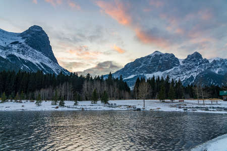Quarry Lake at dusk in early winter season. Sky of pink clouds, snow capped Mount Rundle and Mount Lawrence Grassi in the background. Canmore, Alberta, Canada.