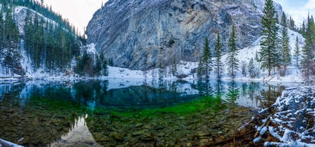 Panorama view of Upper Grassi Lakes in winter season. The reflection of the lake surface like a mirror. Canmore, Alberta, Canada.