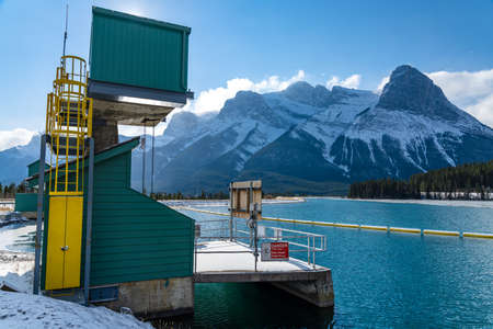 Canmore, AB, Canada-OCT 24 2020: Rundle Forebay Reservoir in winter sunny day morning. Clear blue sky, snow capped Mount Lawrence Grassi mountain range in background.