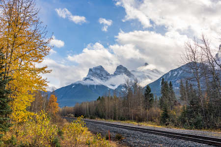 Railway scenery in autumn season, blue sky with white clouds and snow capped The Three Sisters trio of peaks in the background. Canmore, Alberta, Canada.