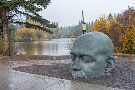 Big Head Sculpture. Town of Canmore Street view in Late fall to early winter season. Canmore, AB, Canada.