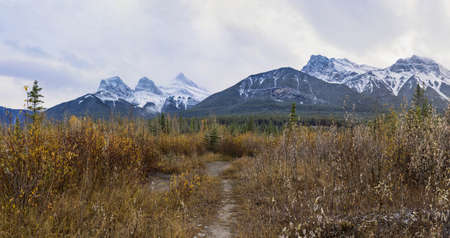 Snow capped The Three Sisters trio peaks and Mount Lawrence Grassi mountain in autumn. Beautiful natural scenery landscape at Canmore, Canadian Rockies, Alberta, Canada.