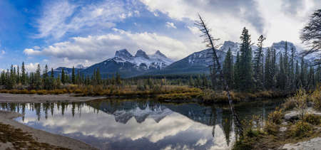 Snow capped The Three Sisters trio peaks mountain with blue sky and white clouds reflect on water surface in autumn. Beautiful natural scenery landscape at Canmore, Canadian Rockies, Alberta, Canada.
