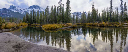 Snow capped Mount Lawrence Grassi mountain with blue sky and white clouds reflect on water surface in autumn. Beautiful natural scenery landscape at Canmore, Canadian Rockies, Alberta, Canada.