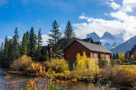 Canmore Opera House and Spring creek, clear blue sky snow capped The Three Sisters trio of peaks in the background. Town of Canmore in autumn season. Alberta, Canada. Sajtókép