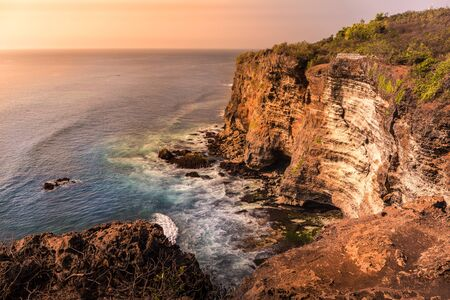 Stunning warm sunset along a cliff coast line in Bali, Indonesia Stock Photo