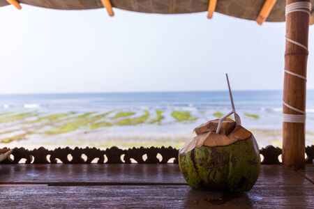 A fresh coconut drink with an tropical beach background at Balangan beach in Bali, Indonesia