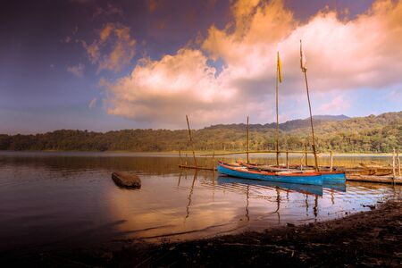 Fishing boats at sunset on the shore of Lake Tamblingan in Bali, Indonesia
