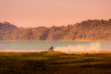 Young boy riding a dirtbike motorbike with a dust trail over a small hill at sunset at Lake Tamblingan in the Bueleng Regency area of Bali, Indonesia