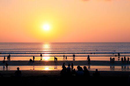 People on Seminyak Beach at sunset in Seminyak, Bali, Indonesia