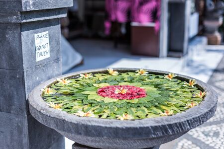 Beautiful Bali offering with pretty flowers and petals outside a stall in Ubud, Bali, Indonesia