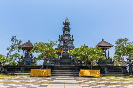 A temple in Bali, Indonesia with pagodas, green trees and a blue sky Stock Photo