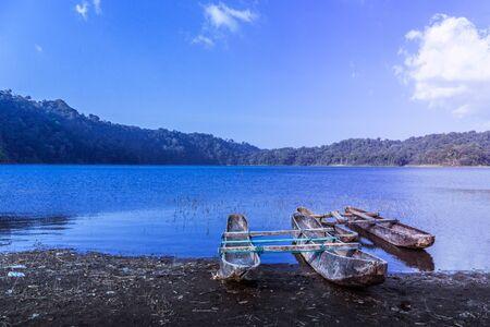 Fishing boats at blue hour on the shore of Lake Tamblingan in Bali, Indonesia