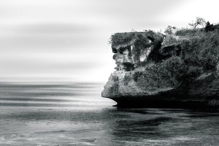 Black and white image of a cliff overlooking the Indian Ocean at Balangan Beach in Bali, Indonesia Stock Photo