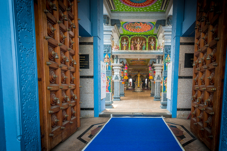 Singapore - October 21st 2015: View into open wooden doors looking towards religious shrines in the colorful and vibrant Sri Srinivasa Perumal Temple on Serangoon Road in Little India, Singapore, Asia