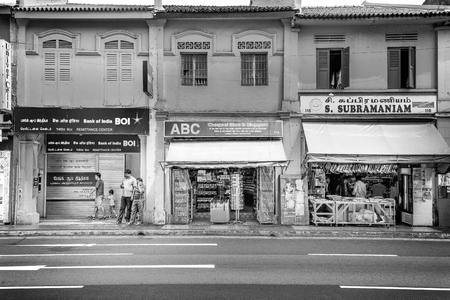 Singapore - October 21st 2015: Black and white image of facades of old buildings and stores lining the street with people inside and outside in the Kampong Glam area of Singapore, Asia