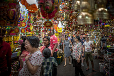 Singapore - October 21st 2015: A crowd of people shopping inside a vibrant and colorful market thats selling decorative gifts and souvenirs in Little India, Singapore, Asia