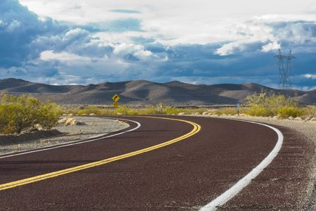 Curved road in the desert with dramatic sky photo