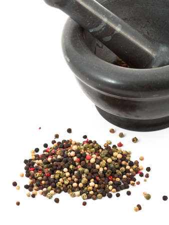 Mixed colored peppercorns with mortar over white background photo