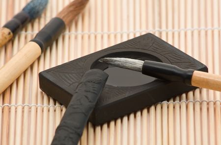 inkstone: Calligraphy brushes with indian ink on bamboo mat Stock Photo