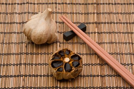 fermented: Whole and cut bulb of black fermented garlic Stock Photo