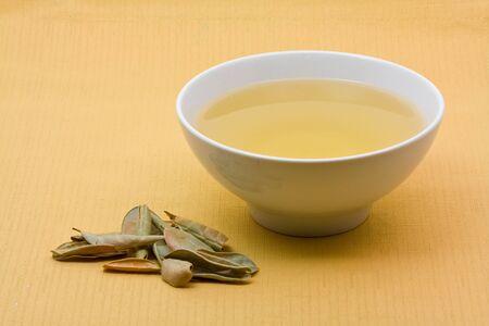 brewed: Freshly brewed herbal tea with leaves over light orange background