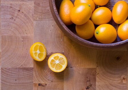 Kumquats whole and cut in wooden bowl photo