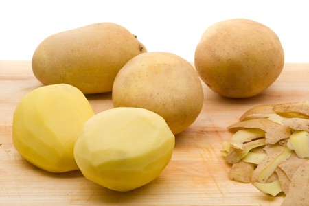 Freshly peeled organic potatoes on cutting board photo