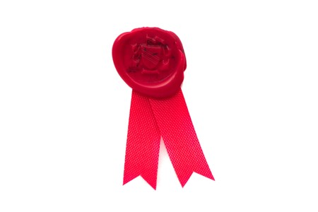 Red wax seal with ribbon over white background photo