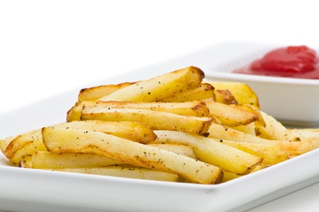 Delicious handmade french fries on plate over white background photo