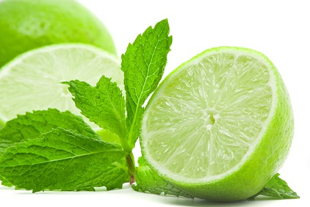 Limes with mint leaves over white background photo