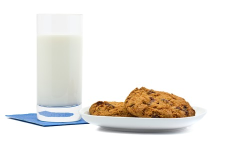 Cookies and glass of milk over white background photo