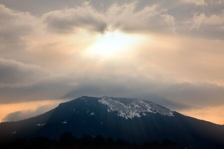 sunrays: God rays during sunset over mountain silhouette