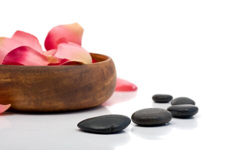 Spa concept of aromatherapy with rose petals and pebbles photo