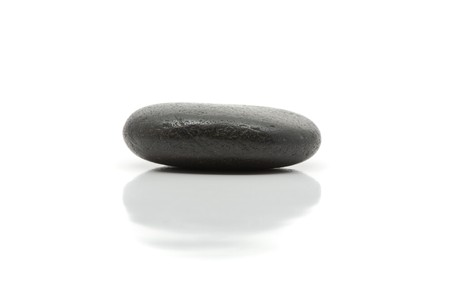 Simplicity meditation concept with single pebble and reflection over white background photo