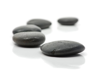 Five pebbles forming a bow over white background photo