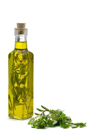 Marjoram infused olive oil over white background photo