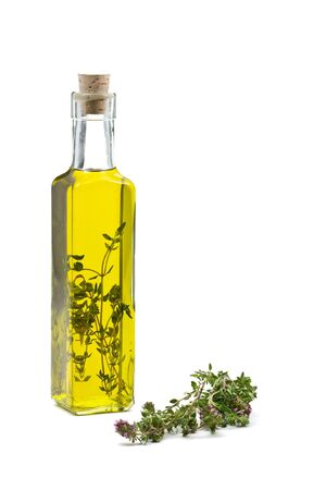 Thyme infused olive oil over white background photo