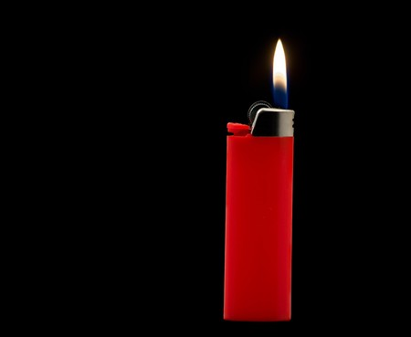 Lit red lighter isolated on black background photo