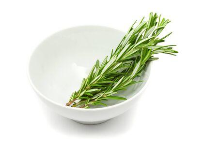 Fresh organic rosemary in white bowl over white background photo