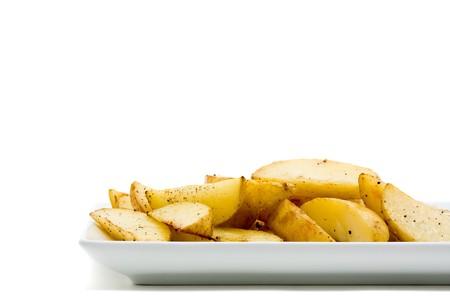 Fresh handmade potato wedges on plate over white background photo