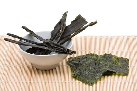 bamboo mat: Kombu and kim nori on bamboo mat over white background