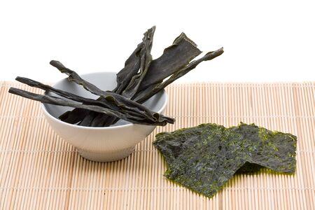 algas marinas: Kombu y kim nori en estera de bambú sobre fondo blanco